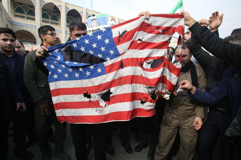 A crowd of Iranians holds up a tattered American flag.