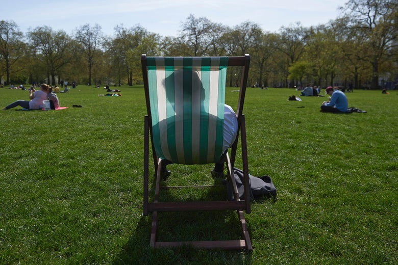 A man relaxes in a deck chair in the afternoon sunshine in the park.
