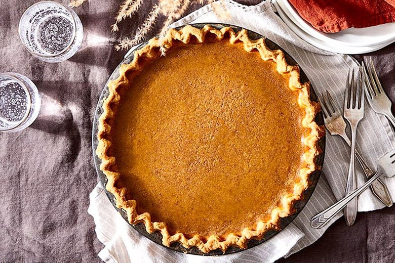 Pumpkin pie set on a tablecloth with forks and glasses of sparkling water beside it