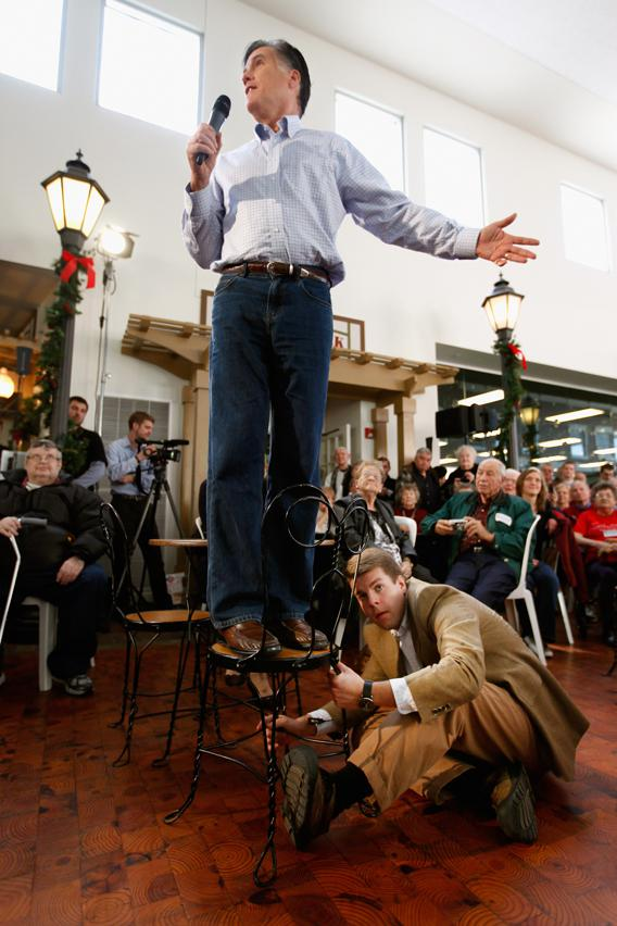 Mitt Romney stands in a chair as campaign staff member Garrett Jackson holds it steady