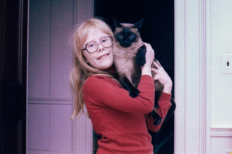 Amy Carter, in a red shirt and glasses, holding her Siamese cat in the White House.