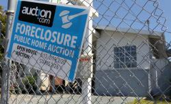 A foreclosure sign hangs on a fence in front of a foreclosed home in Richmond, California.