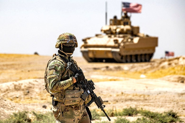 An American soldier wearing a black mask and holding a gun stands in a desert landscape with an American tank in the distance