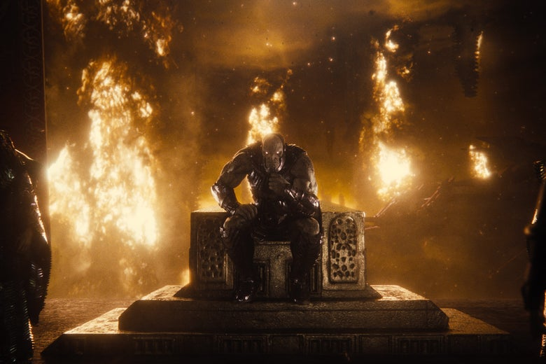 A masked figure sits on a throne in front of a flaming backdrop.