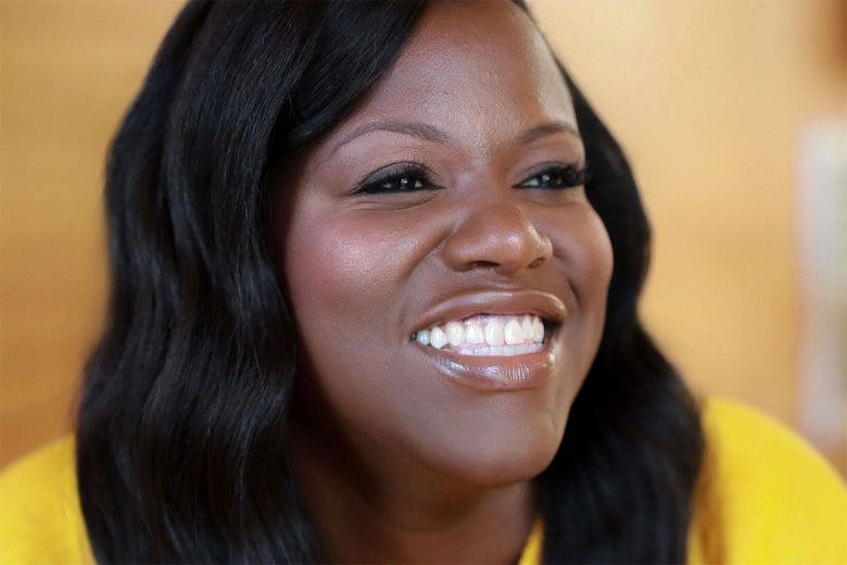 A smiling Black woman.