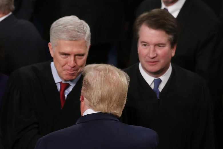Trump, seen from behind, greets Gorsuch as Kavanaugh looks on