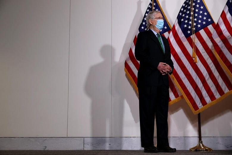 Mitch McConnell, wearing a mask, stands in a hallway in front of American flags, answering questions from the press.