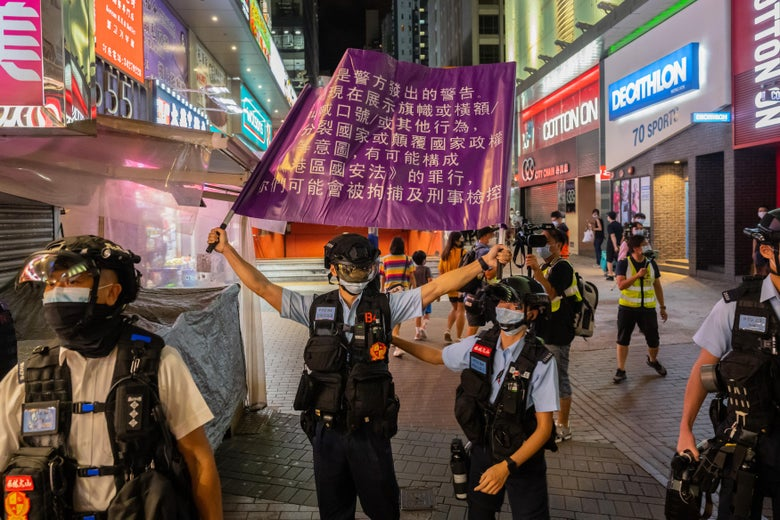 Police raise a purple flag with Chinese characters on it.