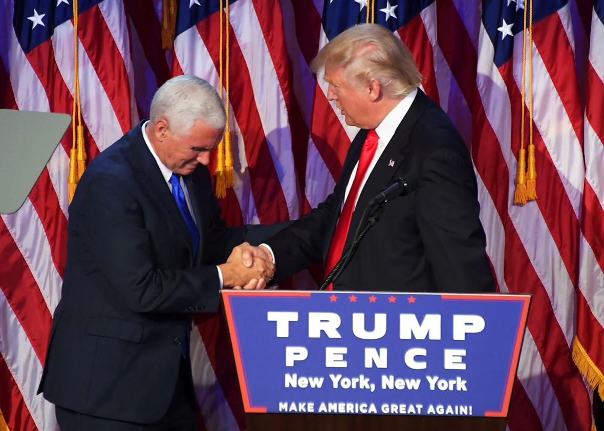 Republican presidential elect Donald Trump shakes hands with Republican candidate for Vice President Mike Pence speak during election night at the New York Hilton Midtown in New York on November 9, 2016.