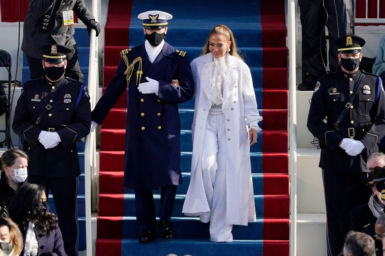 Jennifer Lopez arrives escorted by a member of the military. She wears an all-white outfit with wide-legged pants and a flowy blouse under a long white jacket.