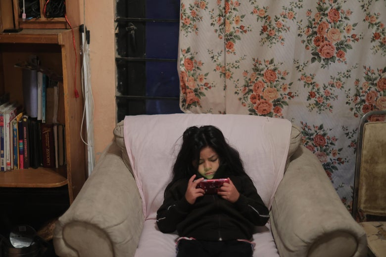 A young girl slumped over in an arm chair stares at a cellphone.