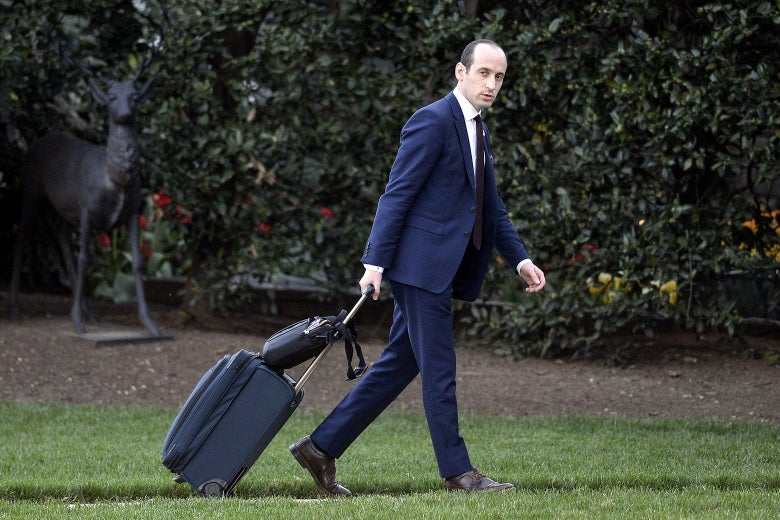 Stephen Miller walks on the White House lawn pulling a roller suitcase.