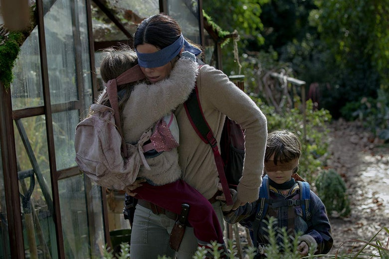 A woman carries a small girl through the forest as a young boy walks alongside them. They are all blindfolded.