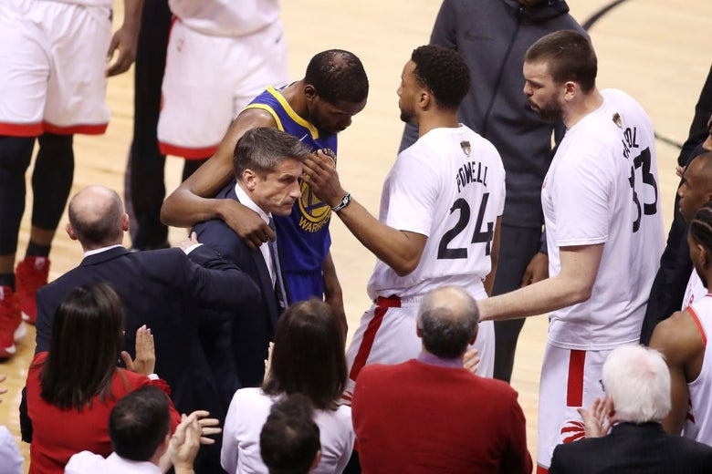 Kevin Durant walks past Toronto players while supported by a trainer.