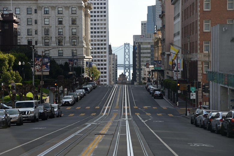 An empty street. The Golden Gate Bridge can be seen in the distance.