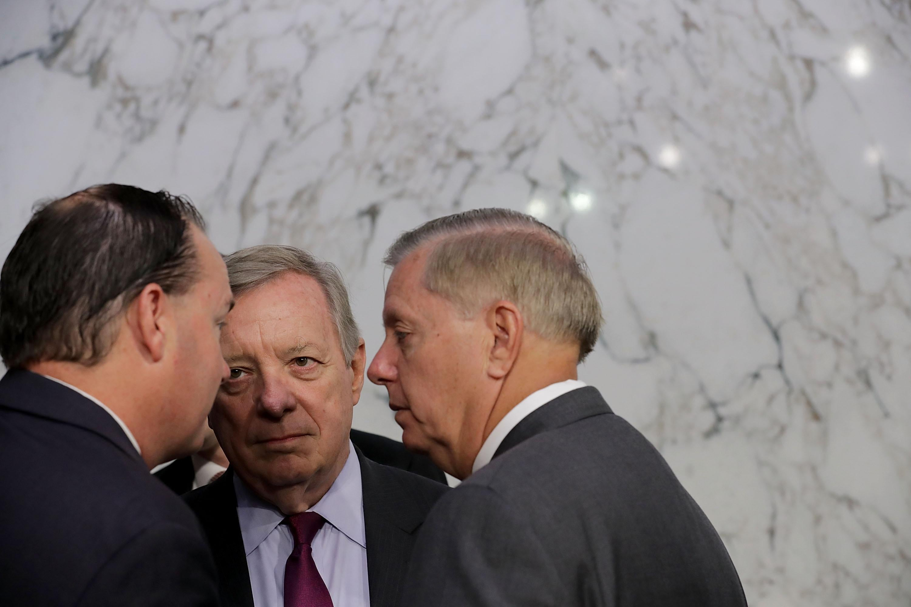 Lee, Durbin, and Graham in a close huddle.