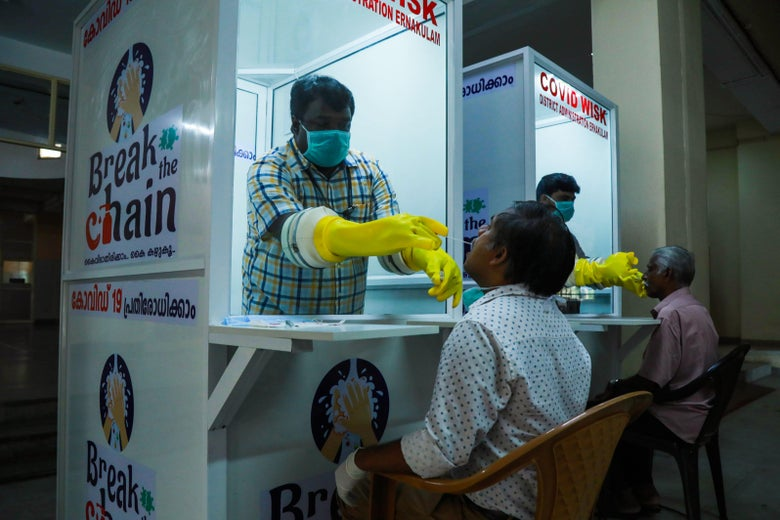 "Two kiosks bearing signs that say ""Break the Chain."" In each kiosk, a medical professional takes a swab sample from a seated person's nose."