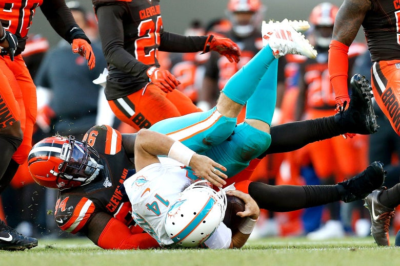 A Cleveland Browns player tackles the Dolphins' quarterback.