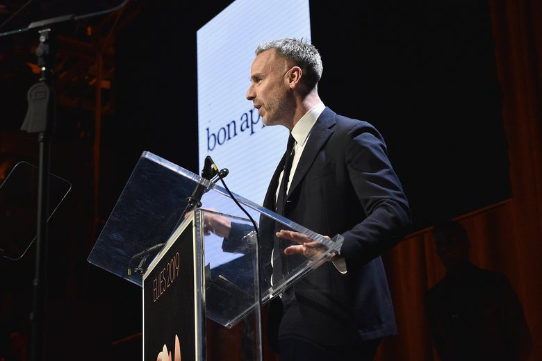 Adam Rapoport speaks on a stage in front of a screen with the Bon Appétit logo.