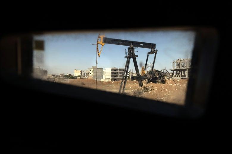 An oil derrick is seen through a small window.