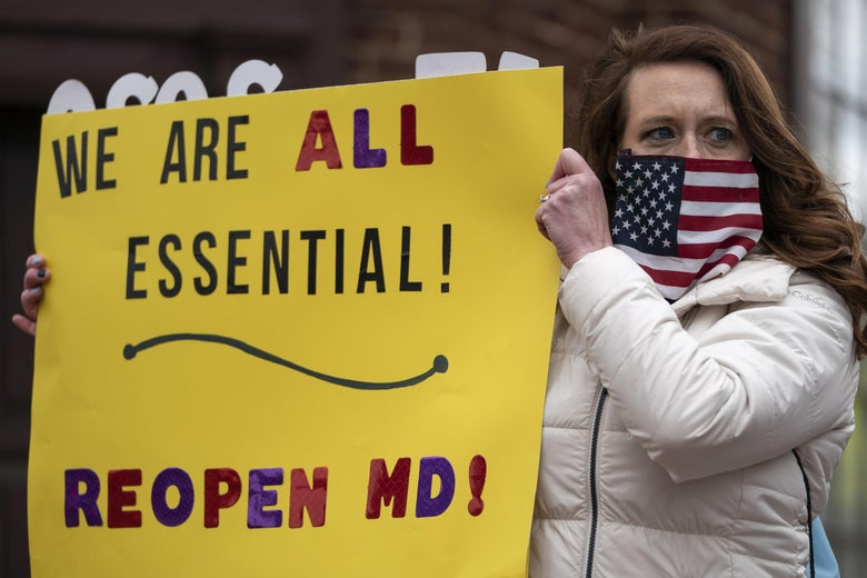 "A protester wearing an American flag face covering holds up a sign that says ""We are all essential! Reopen MD!"""