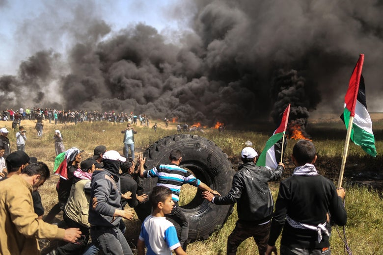 Palestinian protestors burn tires during clashes with Israeli security forces on the Gaza-Israel border following a protest calling for the right to return, east of Gaza City on April 6, 2018.