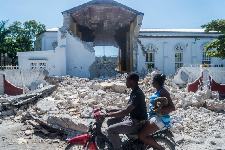 Two people on a motorbike ride past a pile of rubble in front of the husk of the church building