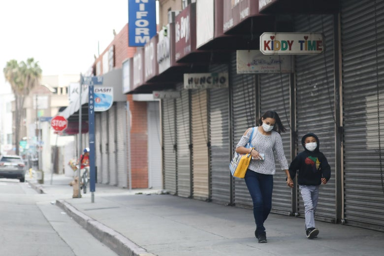 A woman and child walk down a street, both wearing masks.