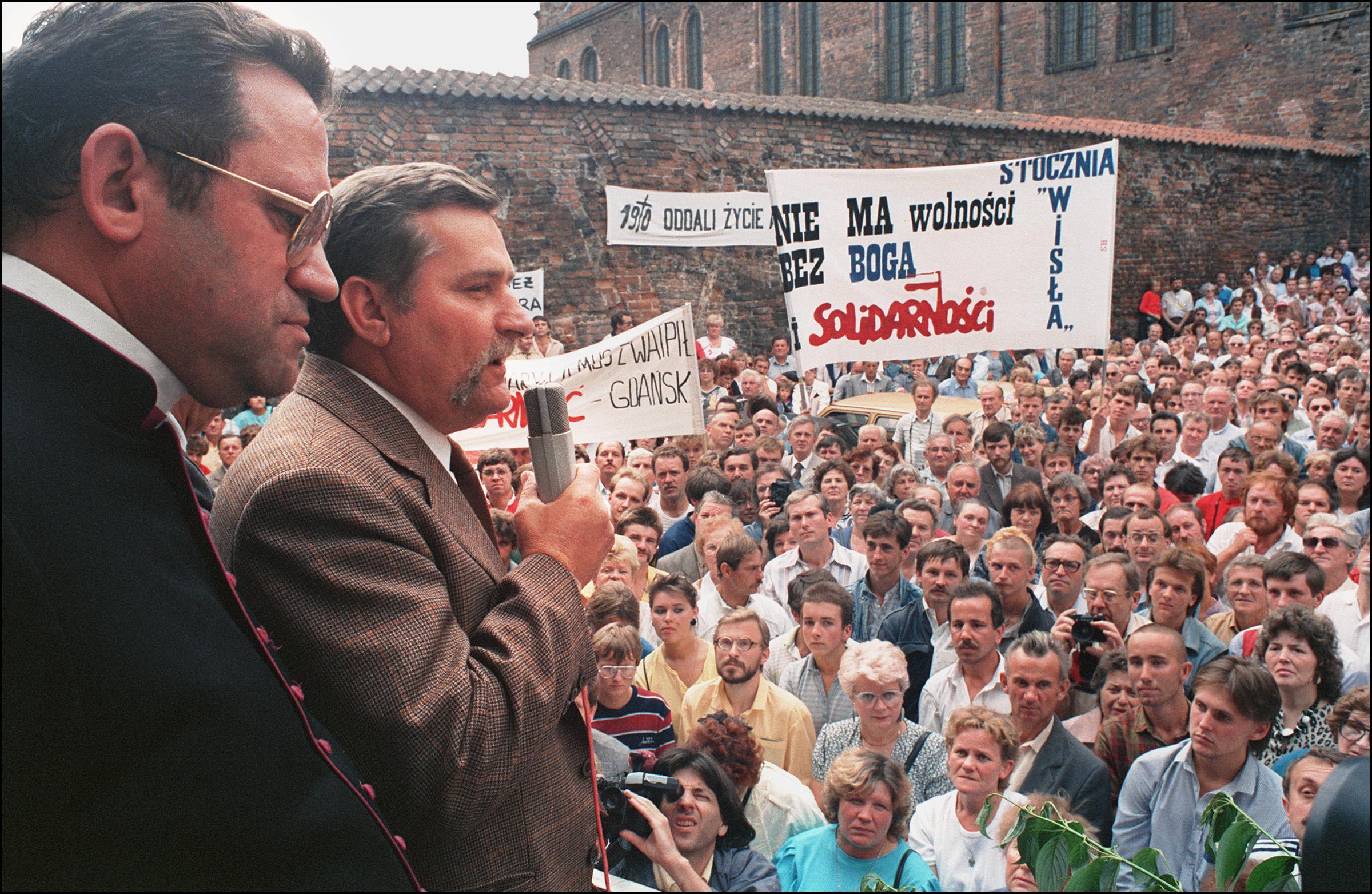 Lech Walesa and Henryk Jankowski address a large crowd of shipyard workers.