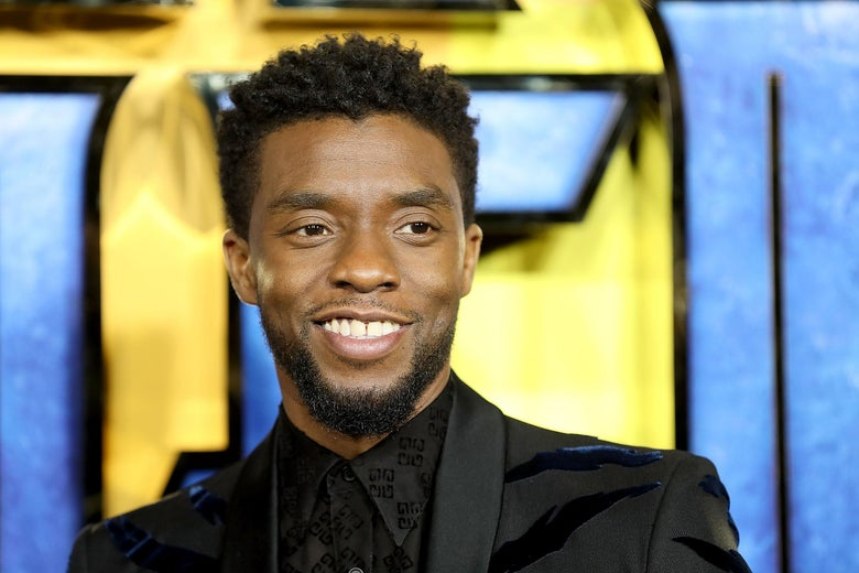 Actor Chadwick Boseman wearing a black suit in front of a blue curtain, smiling.