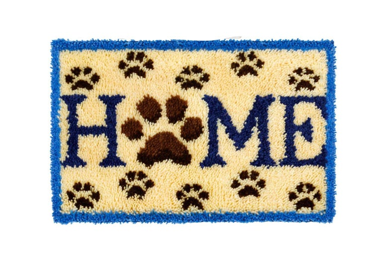 A rug that says HOME with a paw for the O.