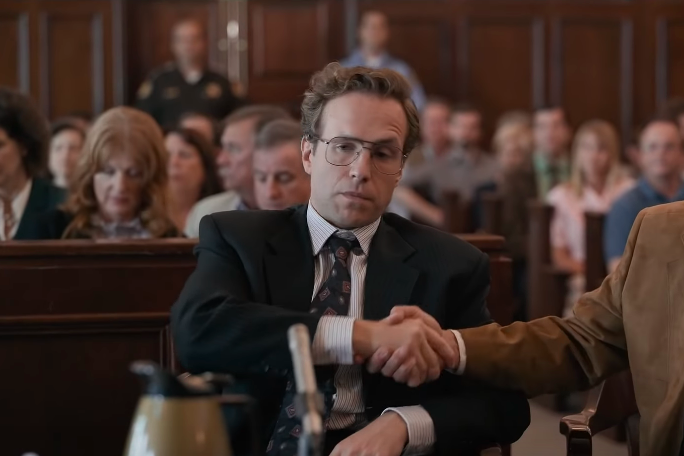 Rafe Spall sits in a courtroom, looking smug,