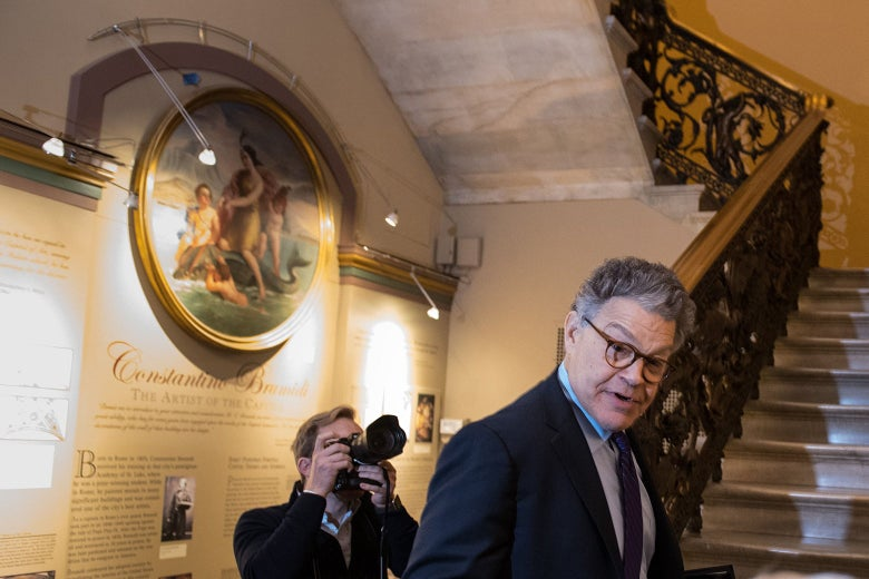 Franken standing next to a staircase in the Capitol as a photographer takes his picture.