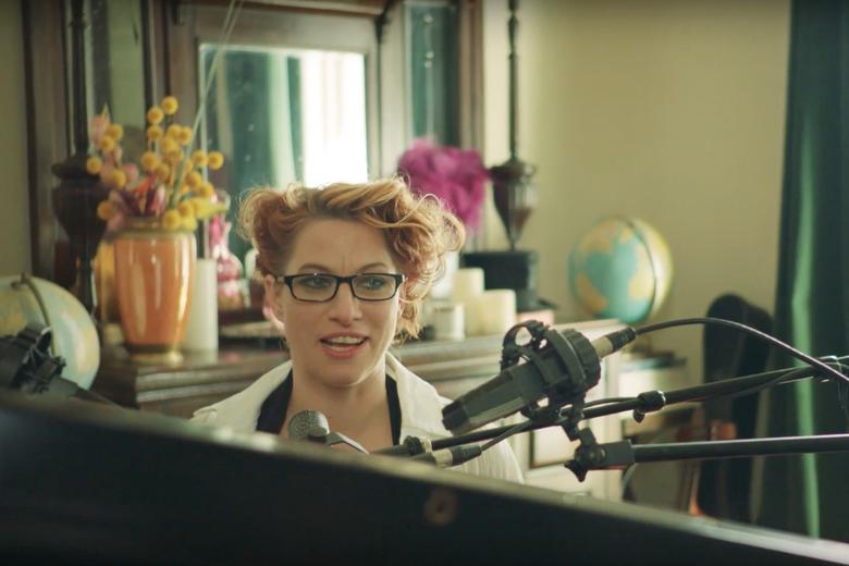 Amanda Palmer sits at a piano