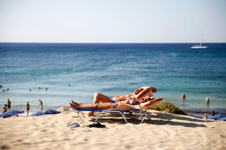 Tourists sunbathe at the beach in the resort town of Ayia Napa in southeastern Cyprus on September 7, 2017.
