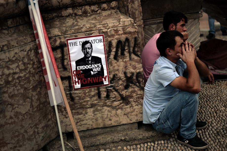 People sit near a poster portraying Turkey's Prime Minister Tayip Erdogan as Hitler in Istanbul on June 5, 2013.