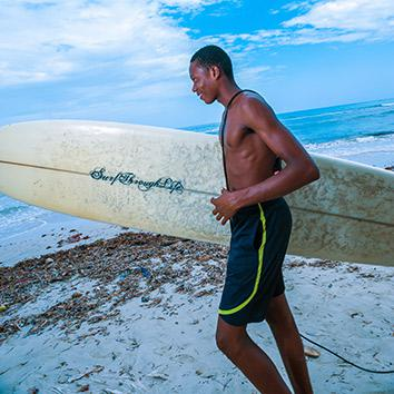 Marco, holding an aptly captioned surfboard, heads down to the water, May 5, 2014.