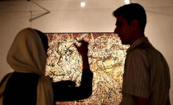 Visitors looks at a painting by 20th century U.S. artist Jackson Pollock.