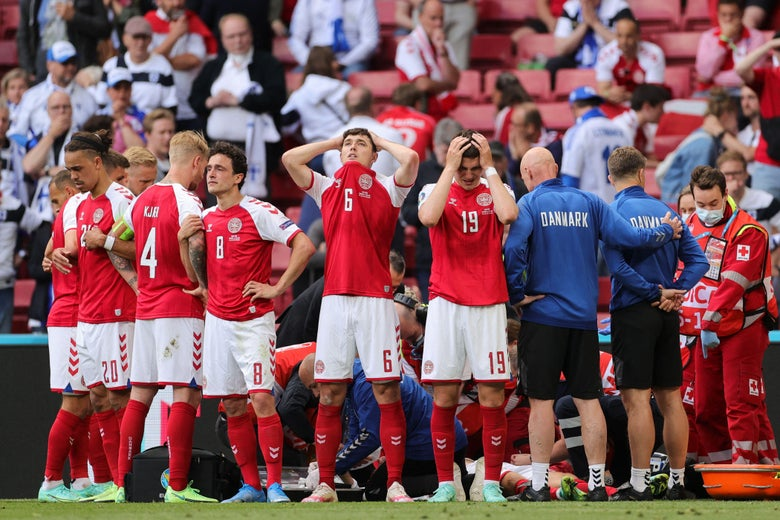 Denmark's players react as paramedics attend to Denmark's midfielder Christian Eriksen after he collapsed on the pitch during the UEFA EURO 2020 Group B football match between Denmark and Finland at the Parken Stadium in Copenhagen on June 12, 2021.