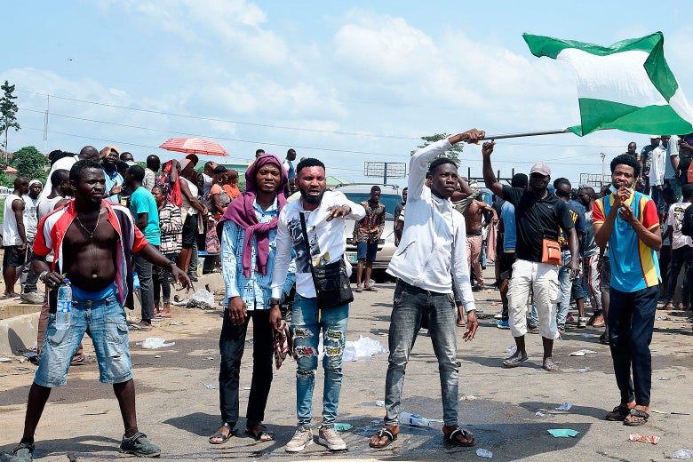 Protesters stand in the middle of the road. One waves a Nigerian flag.