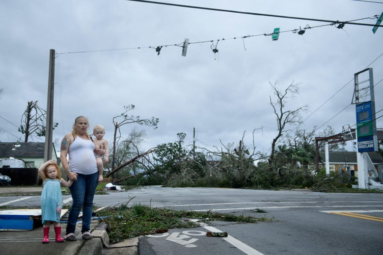A woman holds a baby in one arm and with the other holds the hand of a redheaded girl in rain boots. Behind them, trees have fallen and a gas station is destroyed.