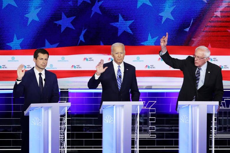 Pete Buttigieg, Joe Biden, and Bernie Sanders raise their hands during the debate.