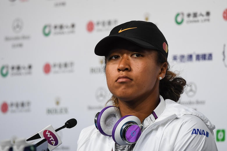 Naomi Osaka sits in front of a microphone.
