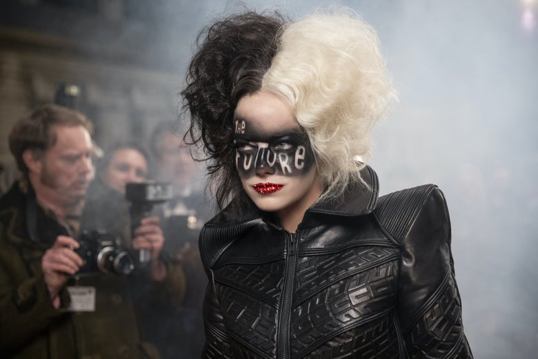 """Emma Stone struts down a runway, curly hair dyed half in black and half in white, wearing a leather top and the words """"The Future"""" painted in soot over her eyes."""