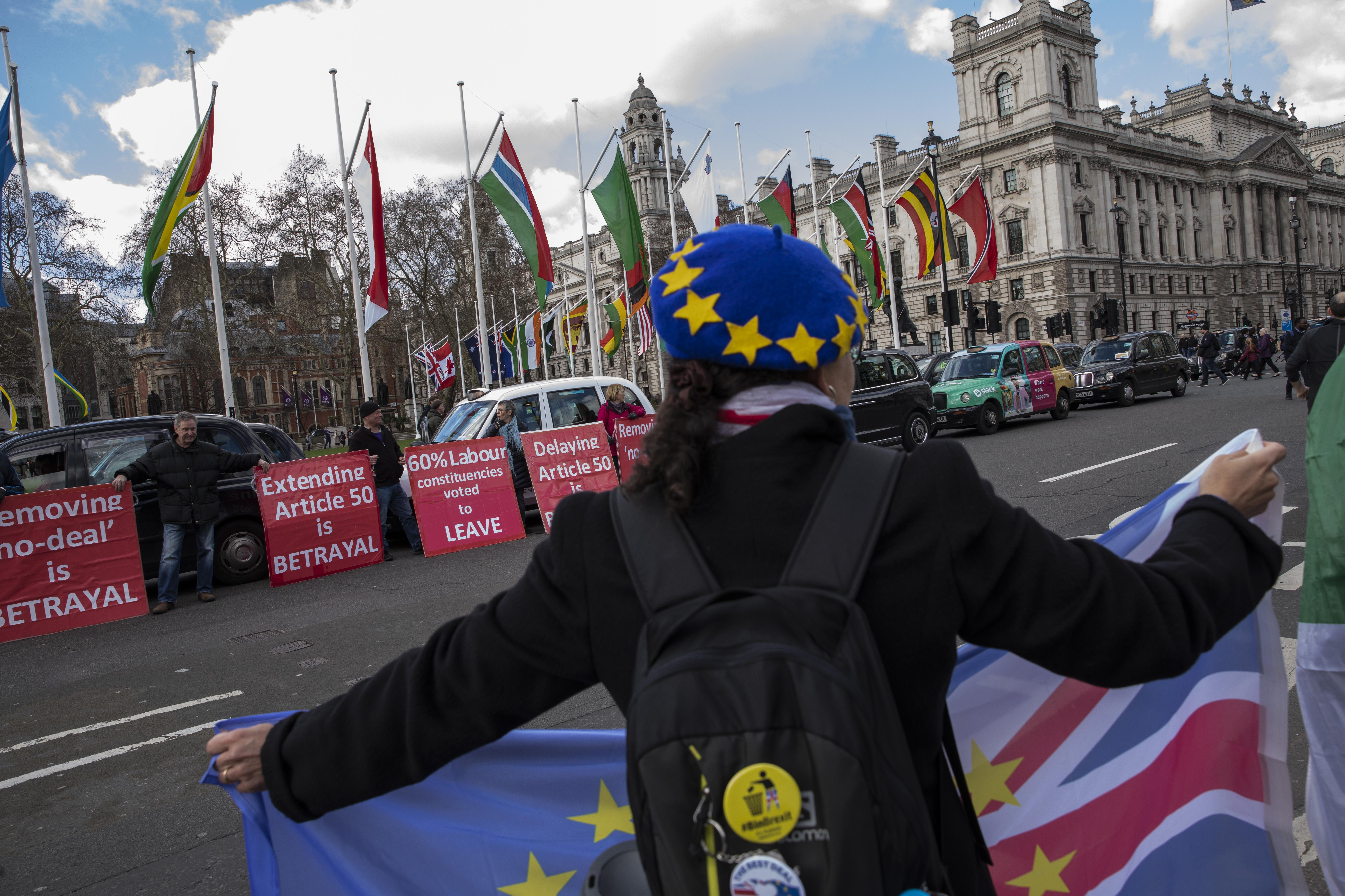 Taxi drivers hold Brexit-themed placards as they stage a Black Cab demo outside the Houses of Parliament in Westminster on Monday in London.