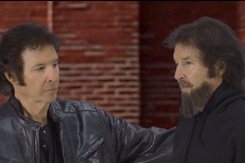 Neil Breen, wearing a leather jacket, puts his arm around Neil Breen, with a beard.