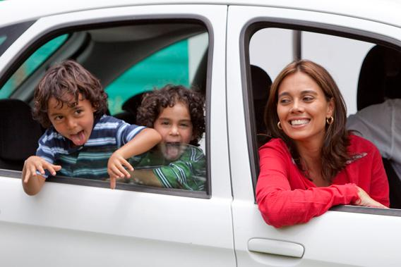 Happy woman and children in car.