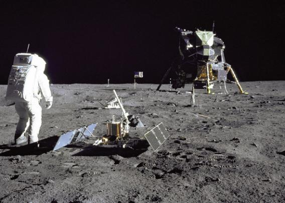Apollo 11 astronaut Buzz Aldrin stands beside a recently deployed lunar seismometer, looking back toward the lunar landing module, 1969.