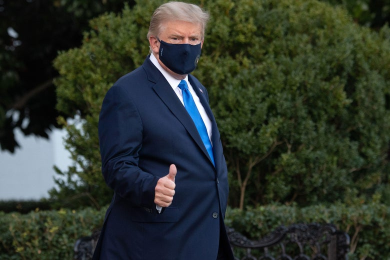 Trump gives a thumbs-up while wearing a mask.