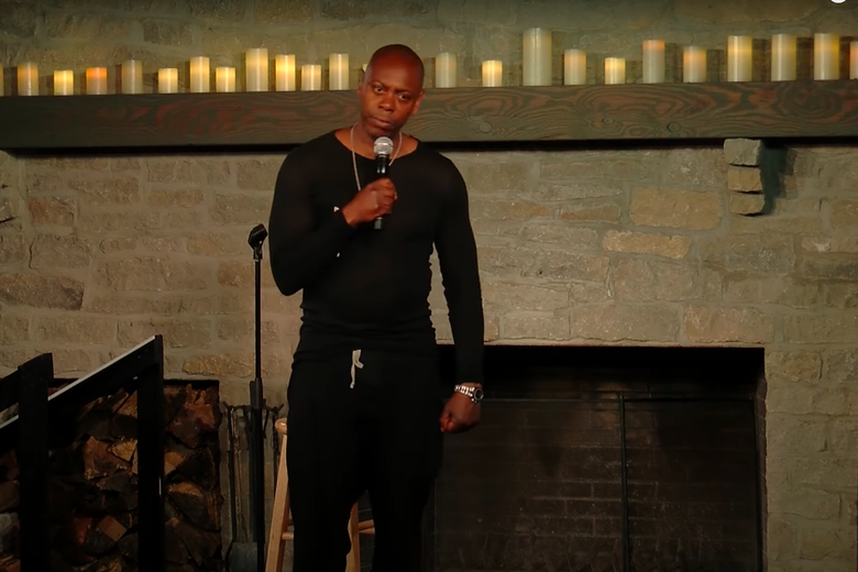 Dave Chappelle standing, one hand holding his microphone and the other clenched in a fist